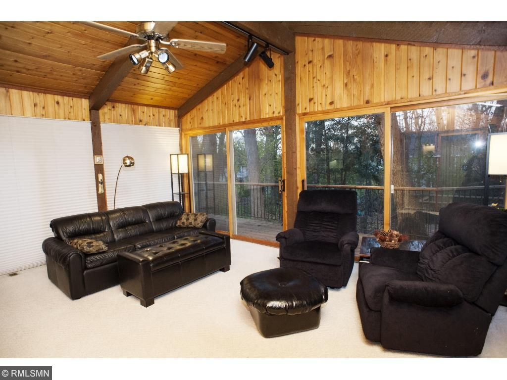 Off the kitchen is a pine paneled three season porch with sliding doors that open to a grand custom deck.