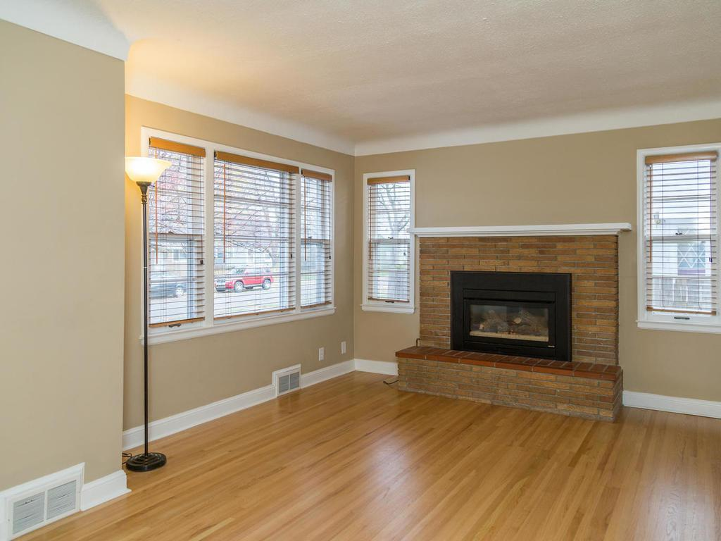 Living room with gorgeous hardwood floors, cozy gas fireplace, and many windows for an open and light filled atmosphere.