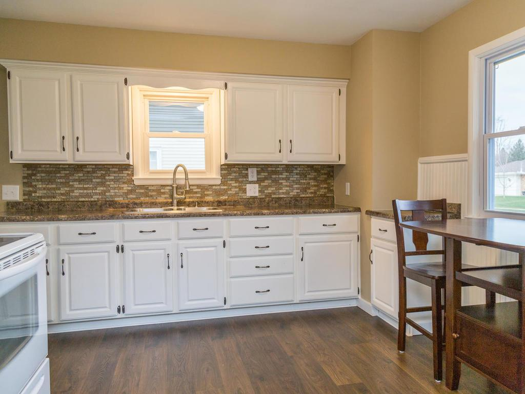 Light and bright kitchen has brand new counter-tops and laminate flooring. Sink with pull-down sprayer.