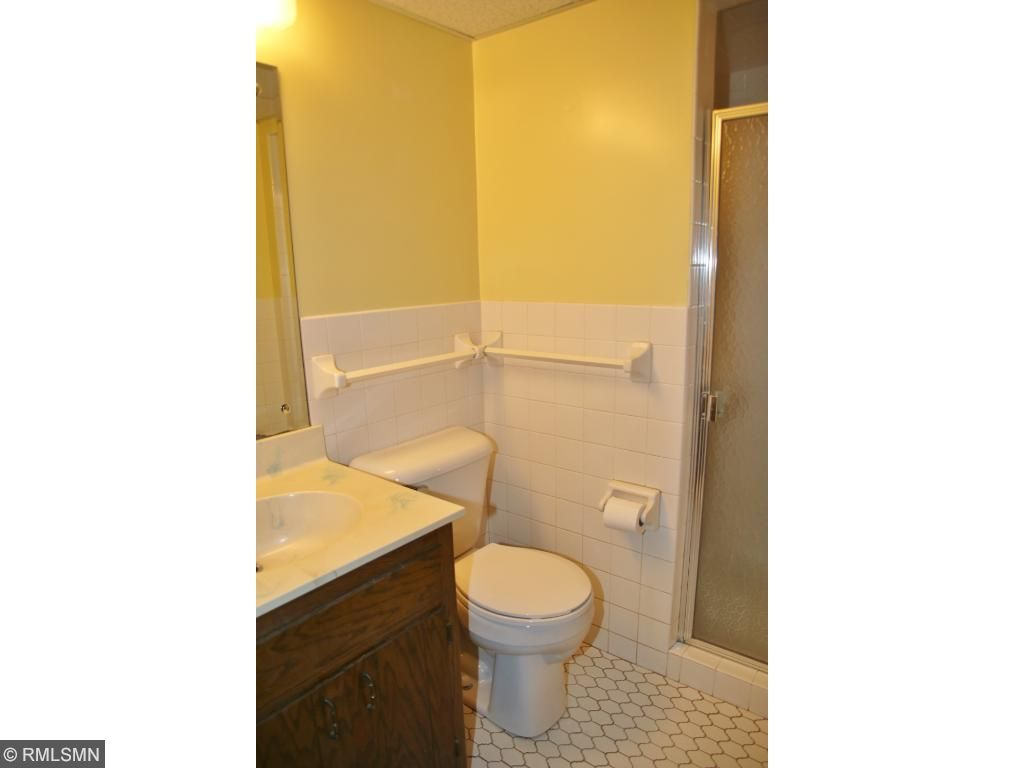 Lower level 3/4 bath has tiled floor and shower stall.