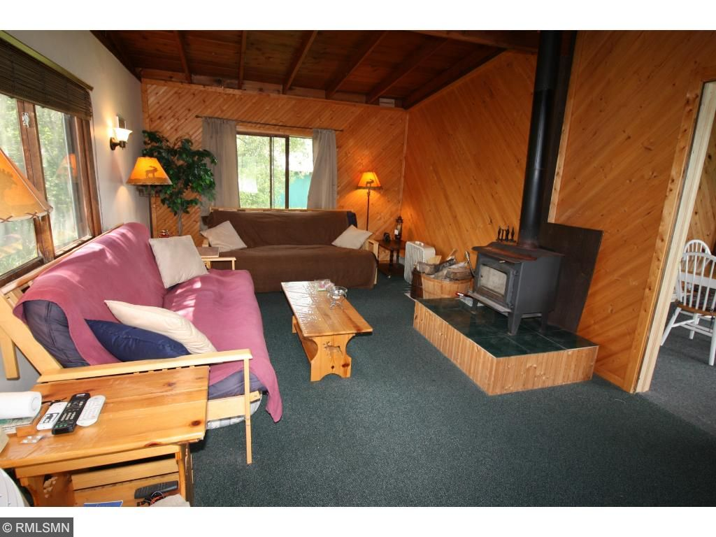 Cozy knotty pine Living Room features a wood stove to keep you warm & toasty.