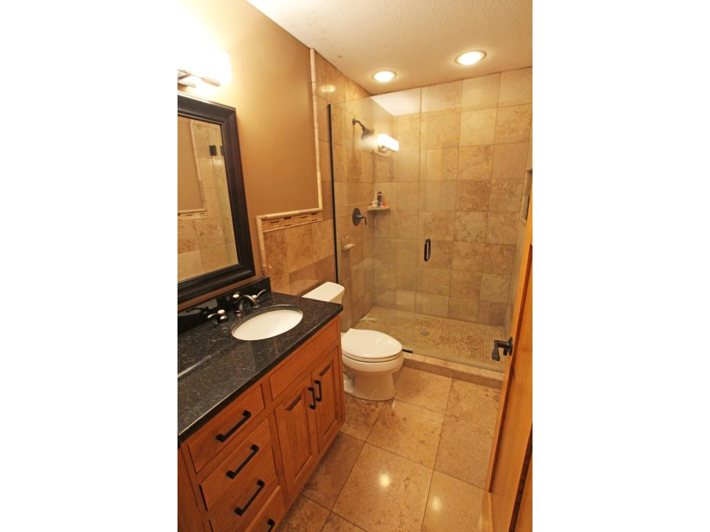 This gorgeous 3/4 bathroom features attractive tile work and also has cozy in-floor heat.