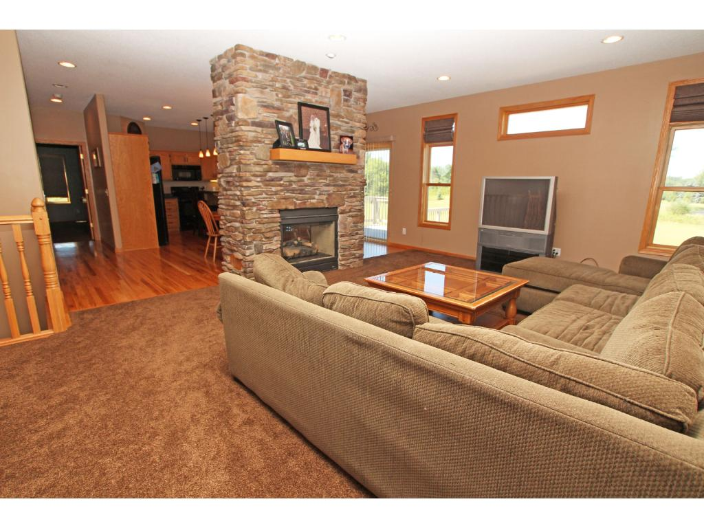 The main floor features three bedrooms and a nice flowing floor plan that is highlighted by the 2-sided stone fireplace seen here.