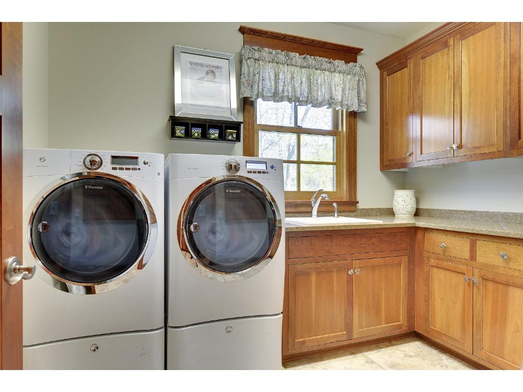The main floor Laundry Room has extensive built-in cabinetry, tiled floors and sink.