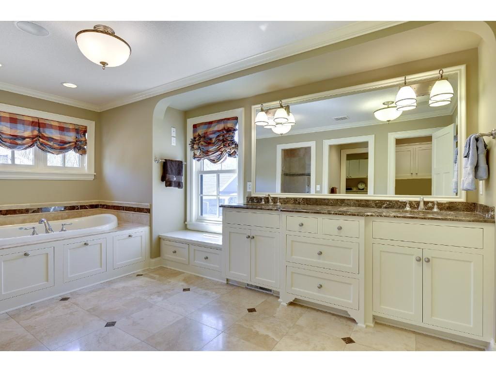 The gorgeous Master Bath has heated marble floors, elevated vanities, a walk-in shower, jacuzzi tub and walk-in closet with custom organizer.