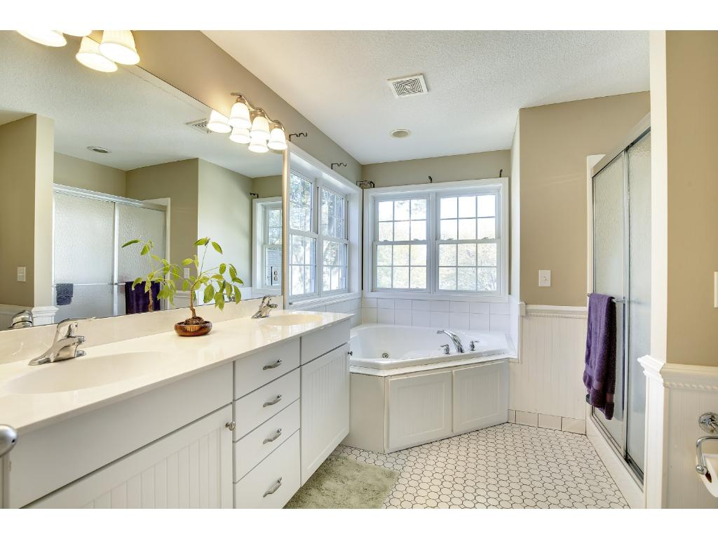 This private full Bath in the owner's suite offers incredible counter space, excellent lighting, tiled floors, and a jacuzzi tub!