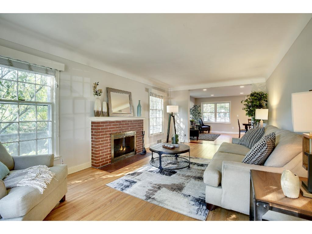 Enjoy the classic brick wood-burning fireplace, paired elegantly with coved ceilings and hardwood floors in this charming Living Room.