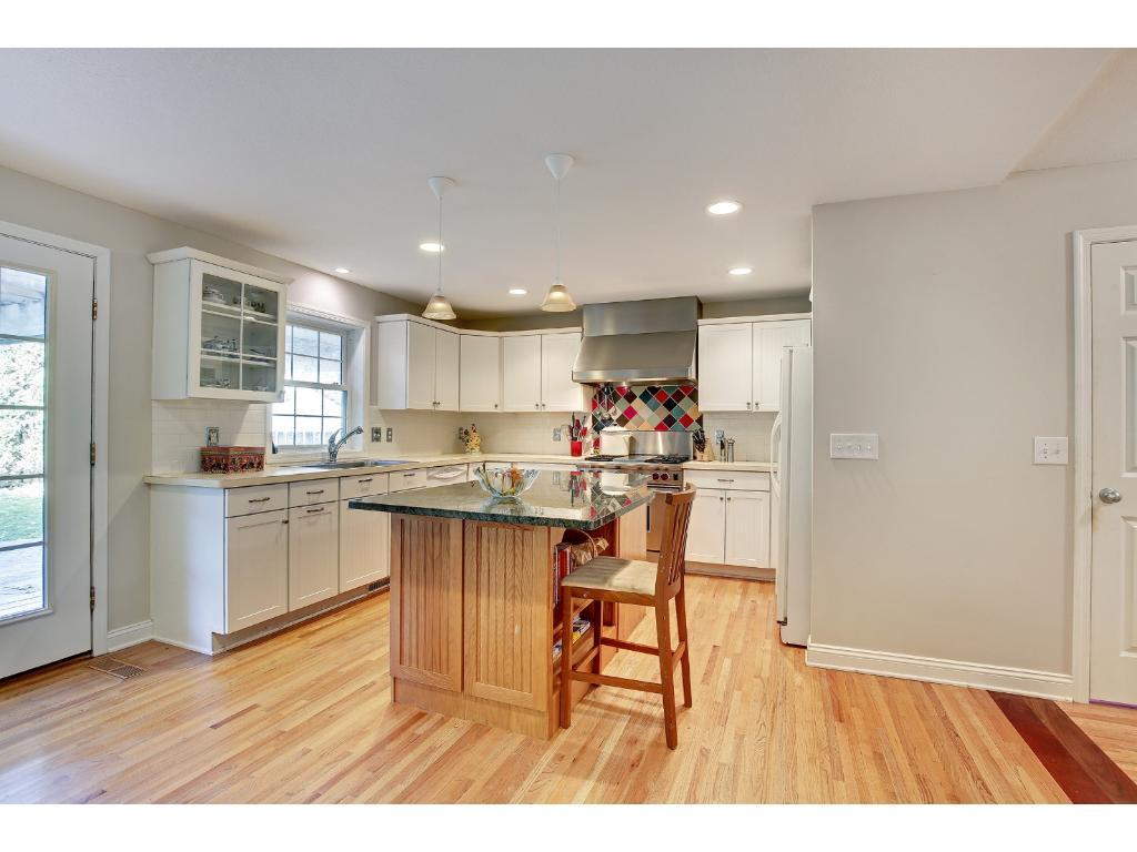 This stunning Kitchen boasts of hardwood floors, inset lighting, granite countertop island, and professional appliances!