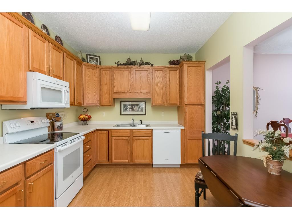 """A very nice kitchen with 36"""" tall cabinets, tall pantry, white appliances, glass top electric stove and nice lighting. Add a small table by the pass through window for a nice seating option or for an additional prep area."""