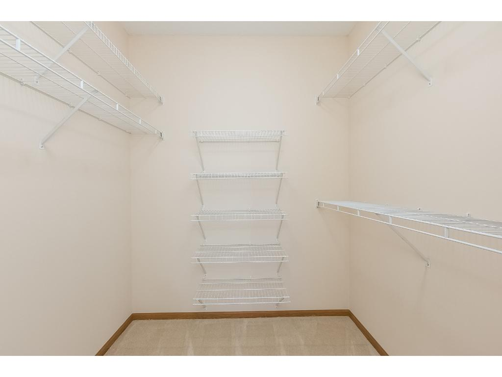 The walk-in master closet has plenty of rod space for hanging items and wire shelves for folded items.