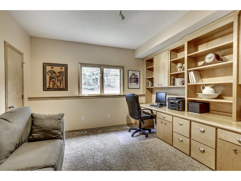 Main level bedroom is currently being used as an office/den and offers a walk in closet and birch built ins.
