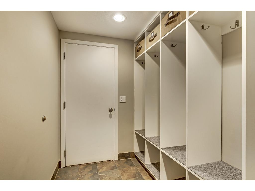 """Current owner's had a section of the garage entry finished and turned in to a mud room that they call the """"locker room"""" with ceramic tile and spacious built ins."""