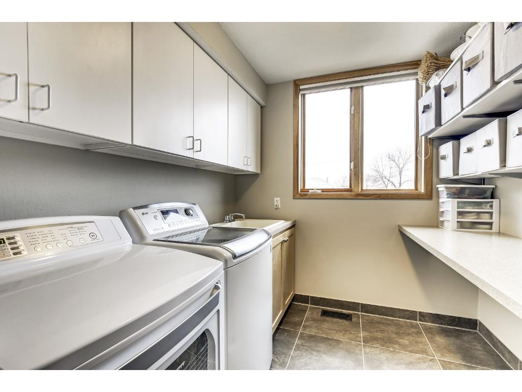 Separate main floor laundry room with cupboards, shelving and folding table. Washer and dryer upgraded in 2014.