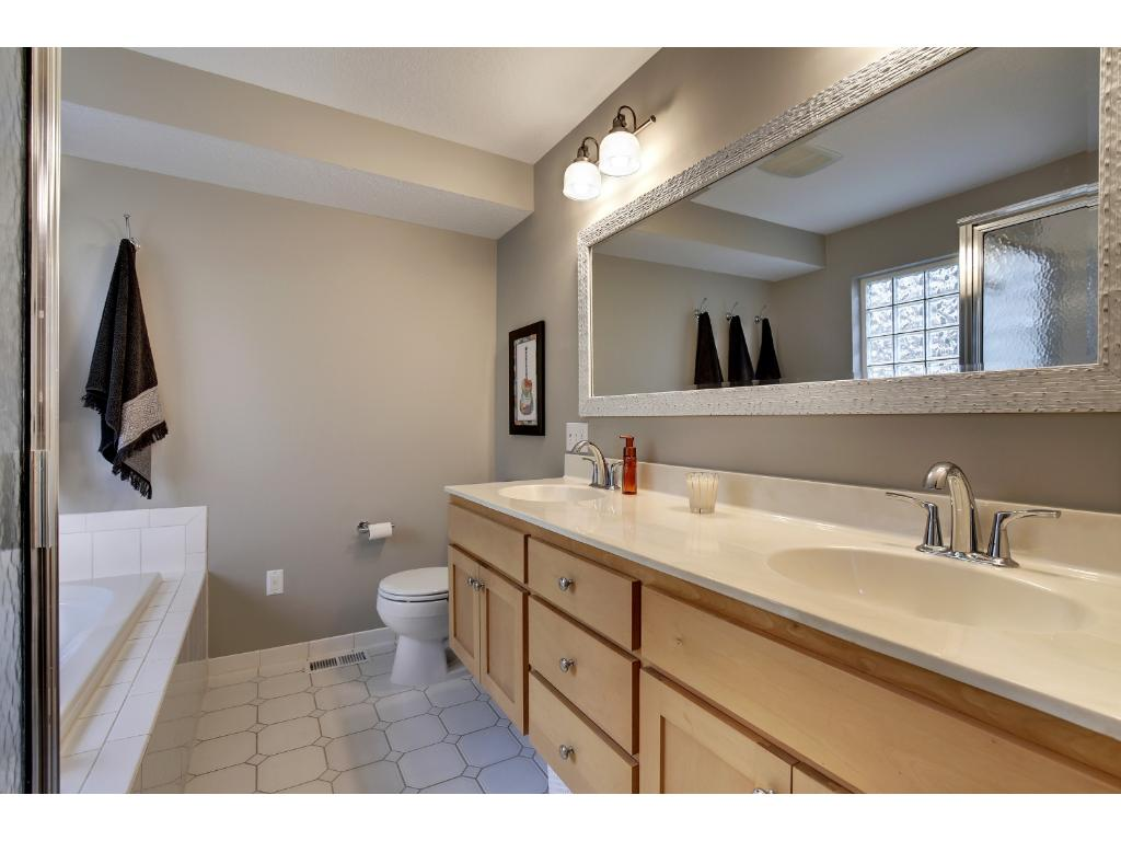 Exceptional private master bath offers dual ergonomic vanity, jetted soaking tub, walk-in shower and under cabinet lighting.