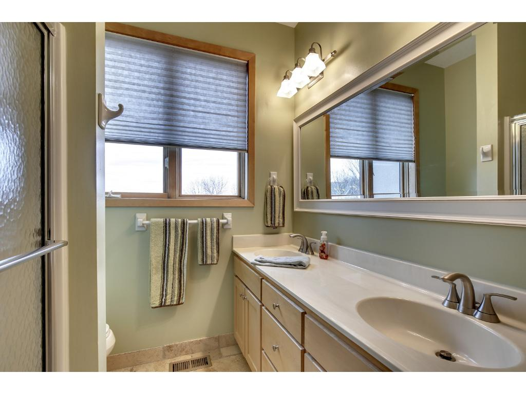 Ceramic tiled full bath on the upper level with dual vanity and sufficient storage.