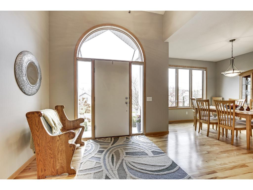 Inviting foyer features vaulted ceiling with transom window, side lights and gorgeous birch floors that flow to the formal dining and kitchen.