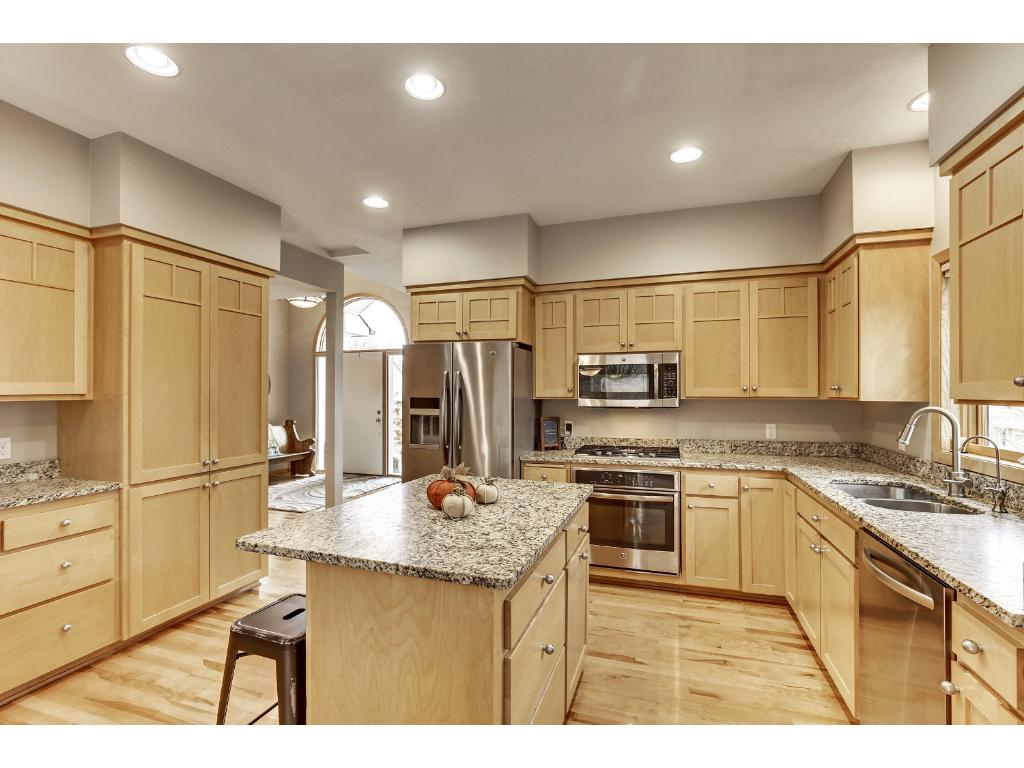 Kitchen includes Venetian Ice honed granite counter tops, stainless appliances updated in 2014, recessed lighting, and large center island with additional storage space.