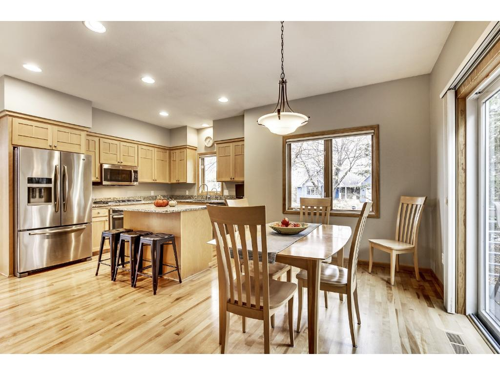 Kitchen also features wood floors, birch cabinets, tons of counter space, ample cabinetry, and is open to the informal dining and living room.