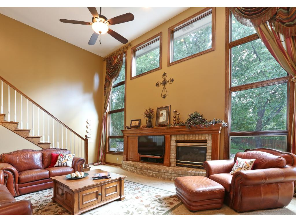 Exceptional vaulted family room with entertainment center, gas fireplace, and views of backyard