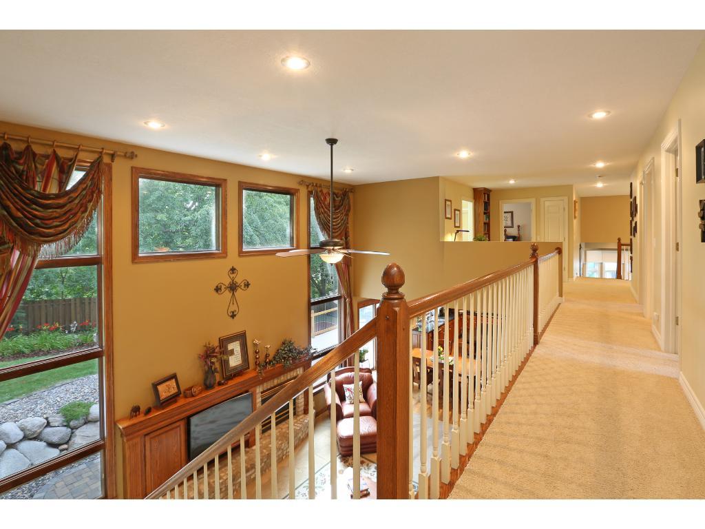 Hallway bridge open to vaulted family room