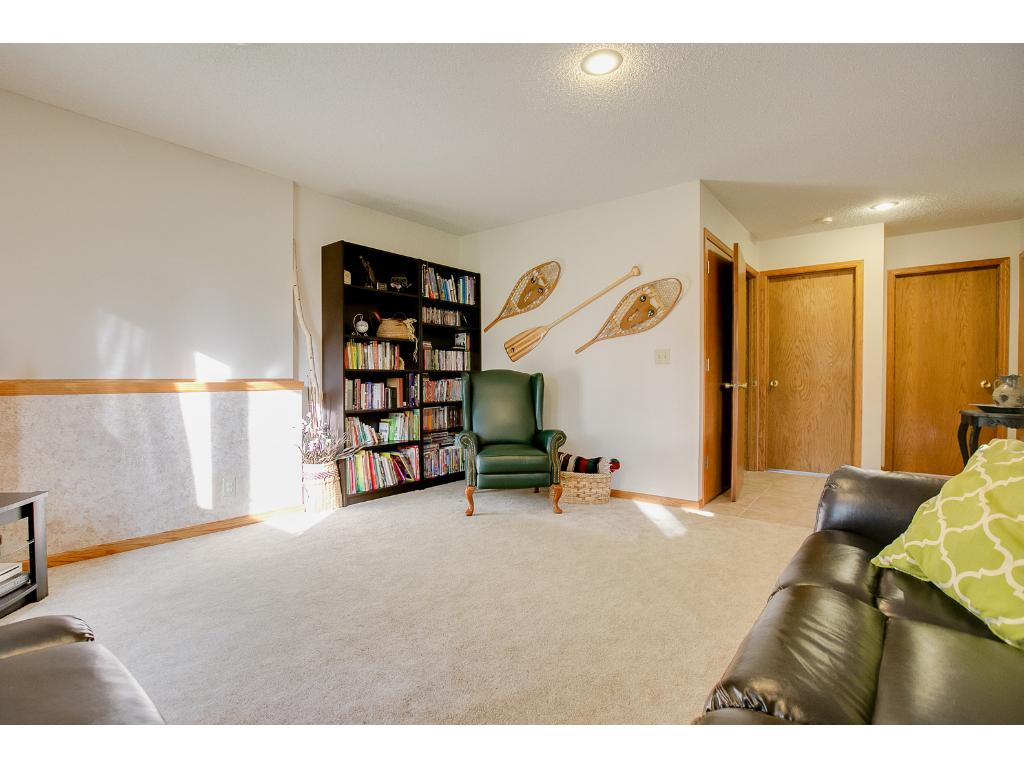 Lower level family room showing the split to the upstairs and door to the large storage area