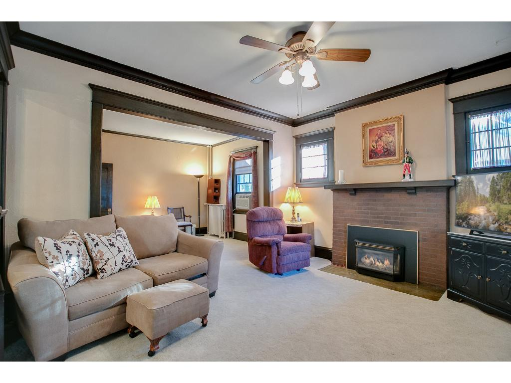 Spacious main floor living room features a cozy brick gas burning fireplace!