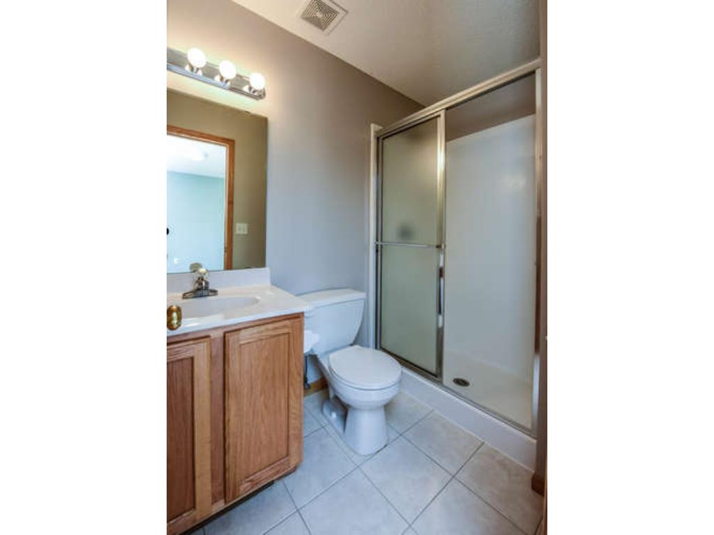 Private 3/4 master bathroom with tile floor.