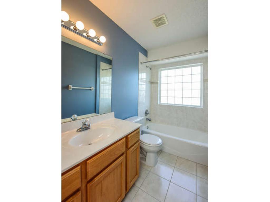 Full upstairs hall bathroom with tile floor and glass block window.