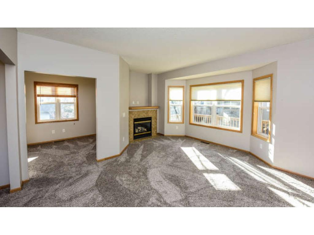 Main floor living room with bay window and tile surround gas fireplace.