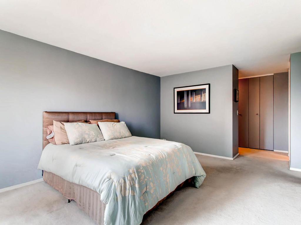 Large master bedroom with roomy walk in closet and back entrance to stairwell.