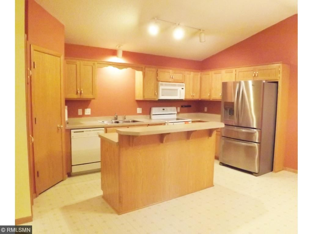 Bright and open updated kitchen with eat-at breakfast bar.  Lots of storage including large refrigerator and food pantry.