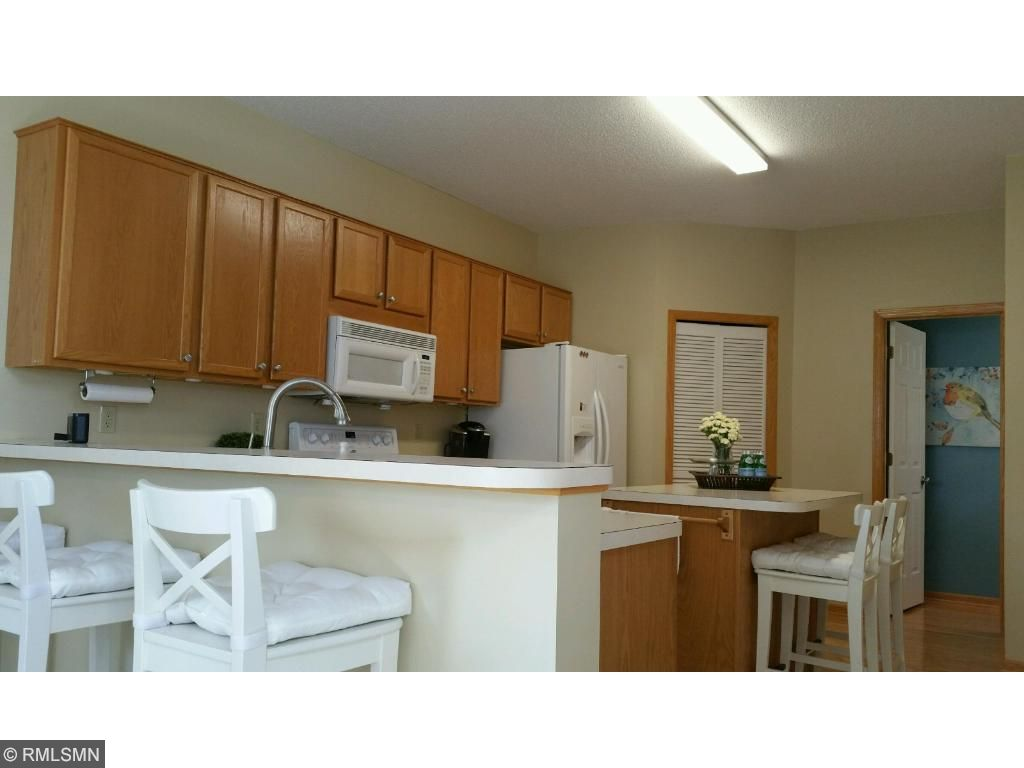 Nice size, bright kitchen with hardwood floors, breakfast bar, center island with additional seating, plenty of cabinet space and large storage closet.  The half bath is off the kitchen area with easy garage access here too!