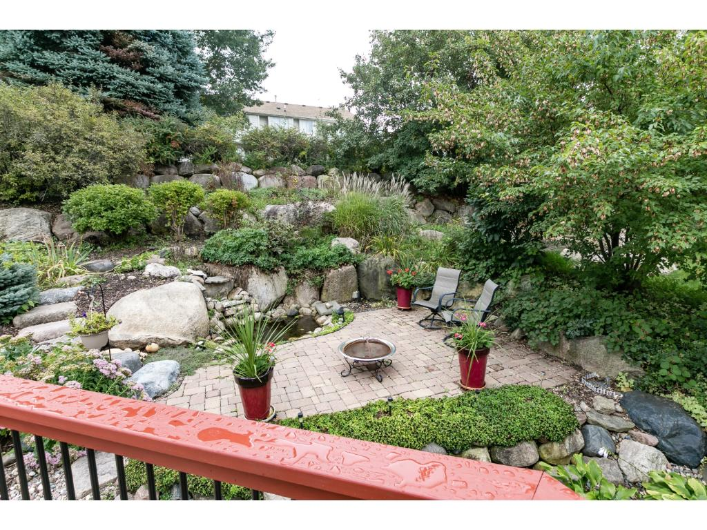 Landscaped back yard with large stone walls, perrenial flower beds and water feature.