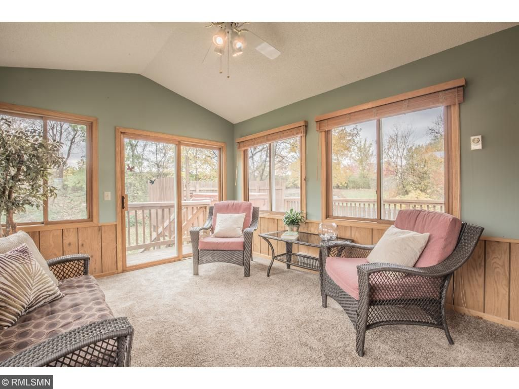 Window wrapped sunroom offers vaulted ceiling with fan and walkout to deck.
