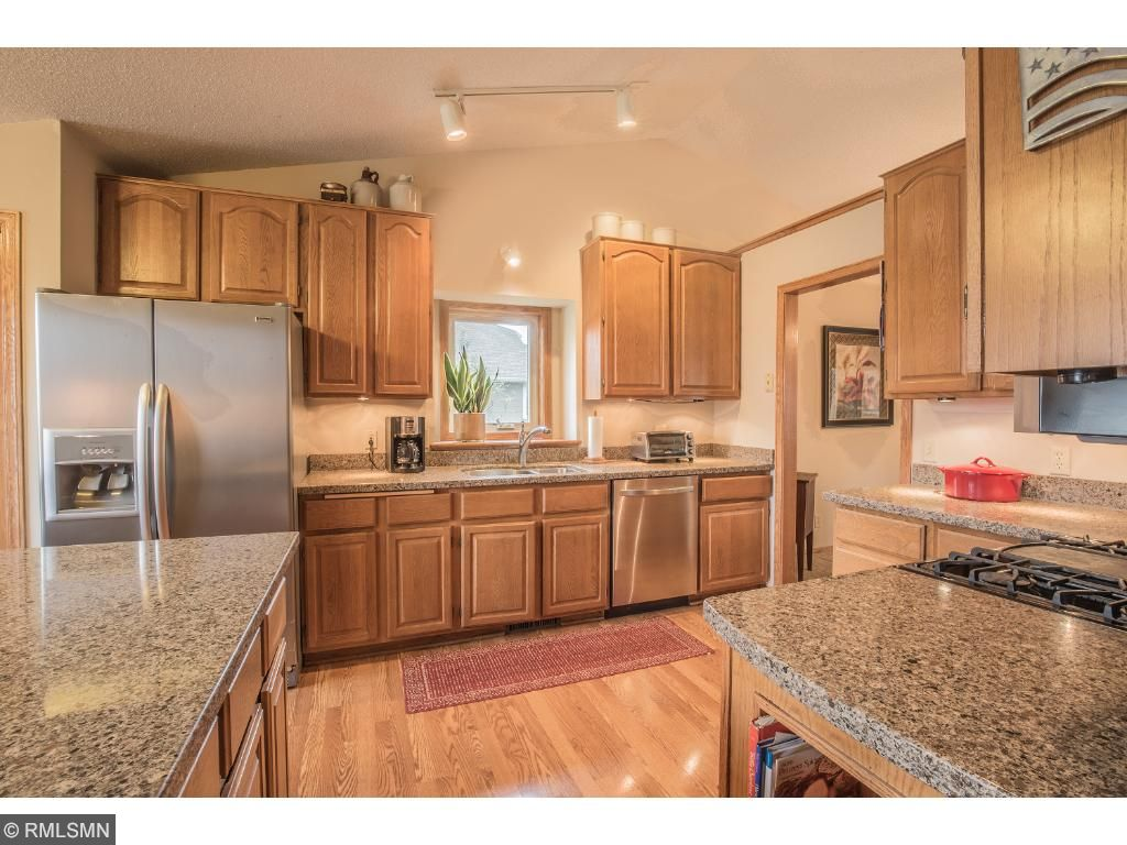 Kitchen features ample cabinetry, above the sink window, center island, quartz countertops and stainless steel appliances.