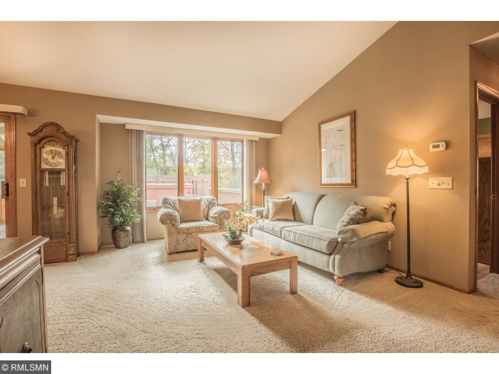 Vibrant living room with private views, vaulted ceiling with fan, and abundant natural light.