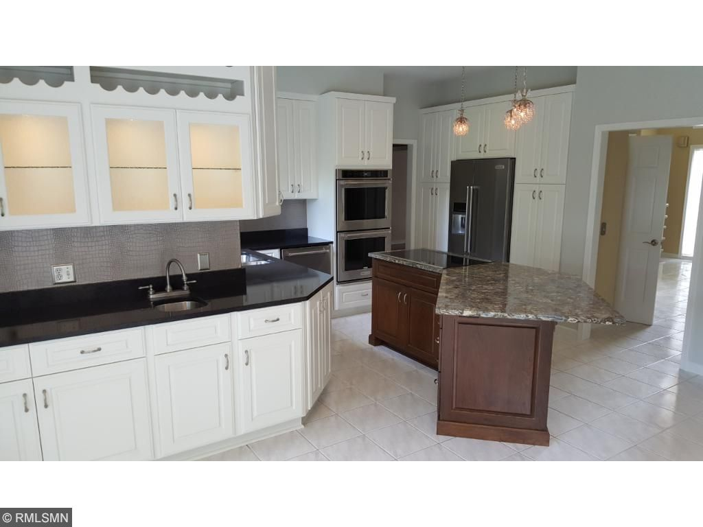 Newly remodeled kitchen with a cherry center island surrounded by white cabinets