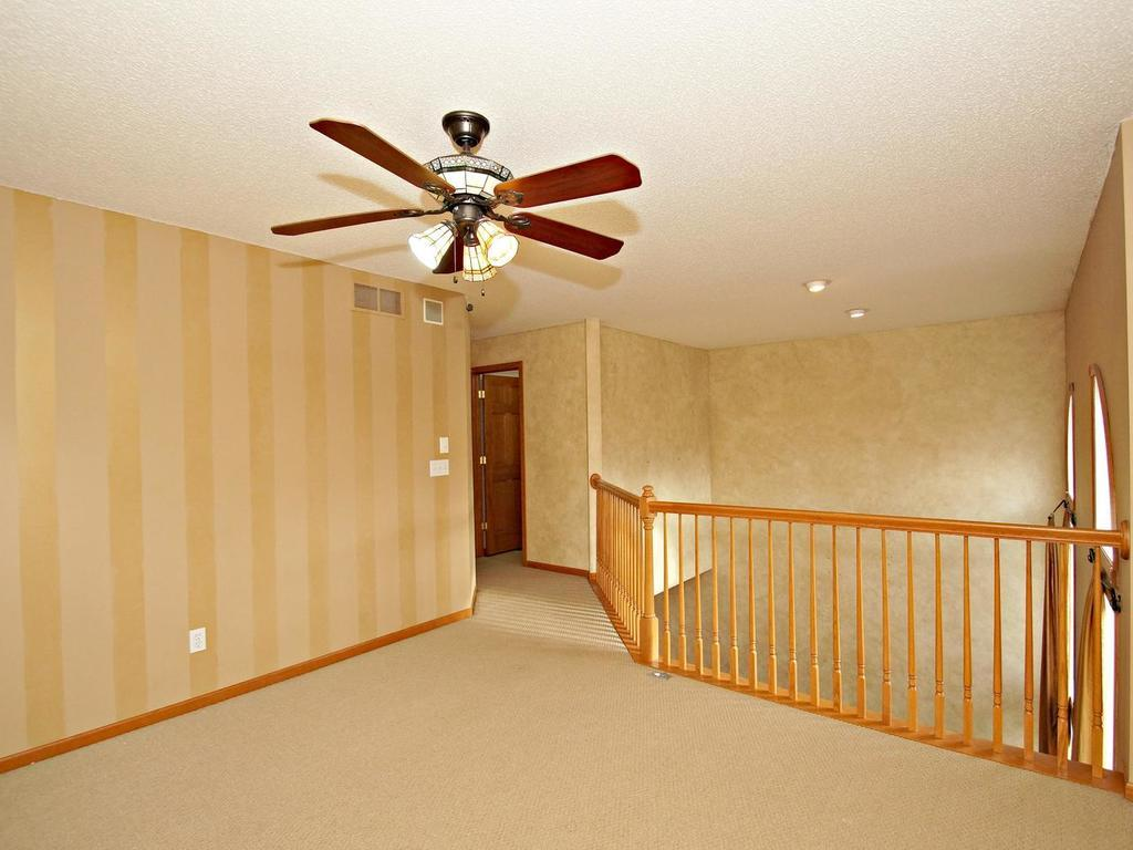 Large loft on the upper level with upgraded wood railing and ceiling fan.
