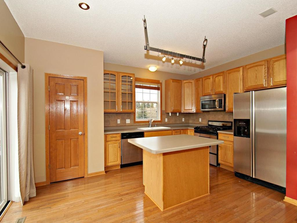 Chef's kitchen with large pantry, island and sparking stainless steel appliances.
