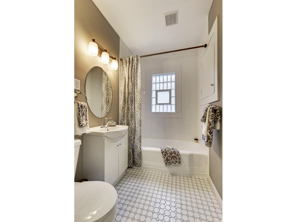 Main floor full bath freshly remodeled with aglass block window, subway tile tub surround and ceramic tile floor.