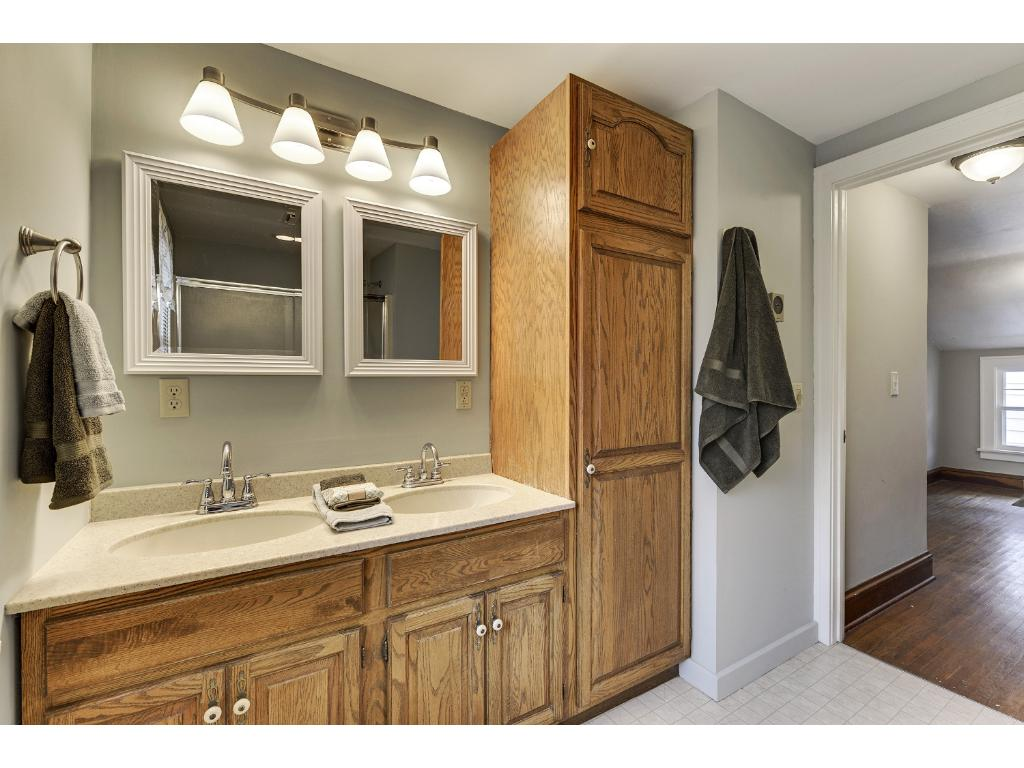 Upper level full bathroom features a double vanity with a linen cabinet.