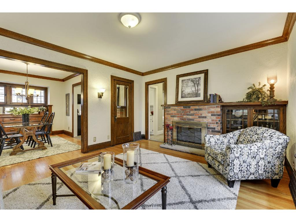 Spacious living room features a charming Chicago brick fireplace with built in curio cabinet, Oak mantle, cove molding, large window seat and beautiful hardwood floors.