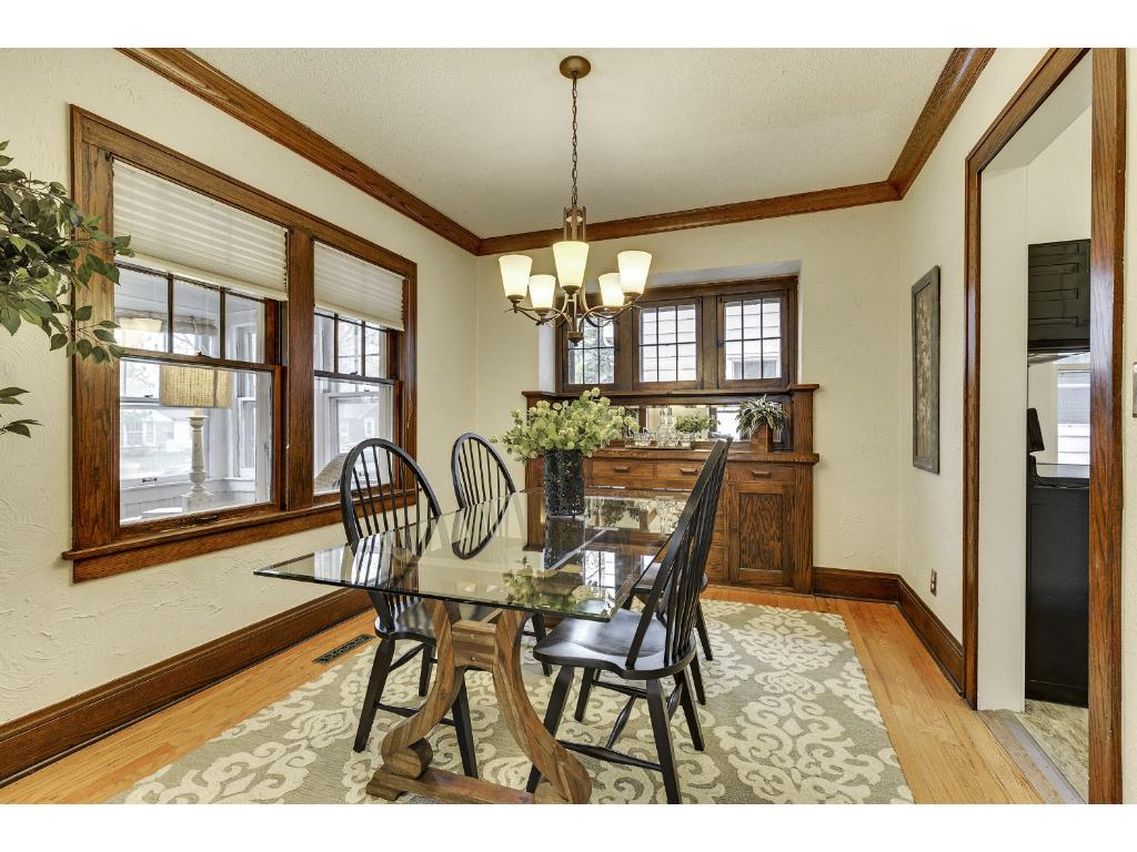 Formal dining room features a beautiful built in buffet,  cove molding, and hardwood floors.