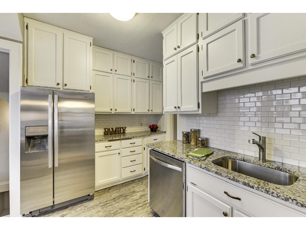 Kitchen features new stainless steel appliances, new flooring,  granite counter tops, Ceramic tile back splash and a generous amount of white cabinetry.