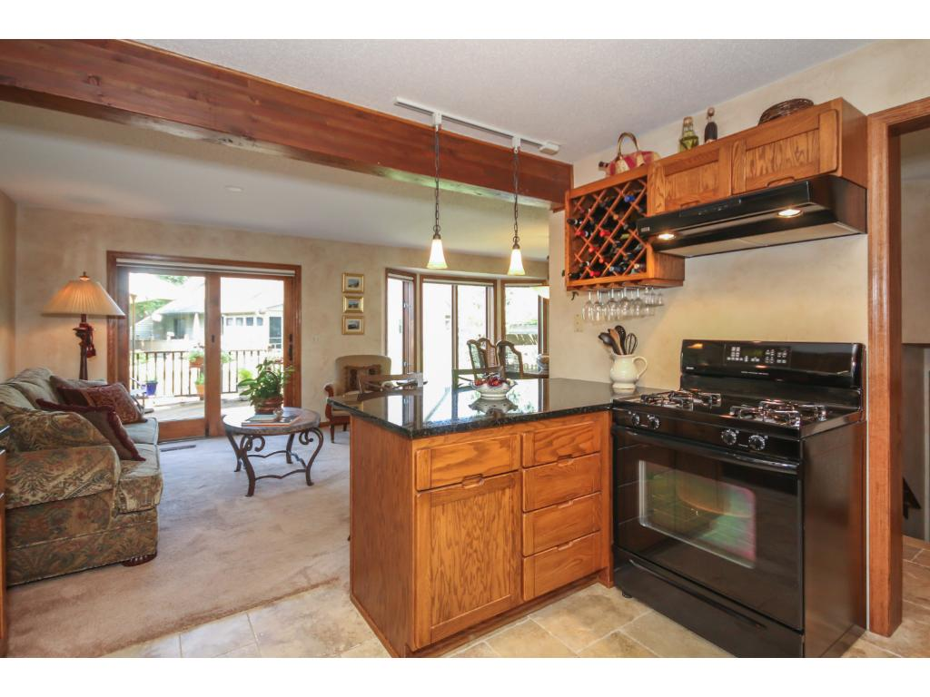 Open, main floor design flows from the beautifully updated kitchen, through the sitting/dining room out to the large deck and patio with pretty pond views!