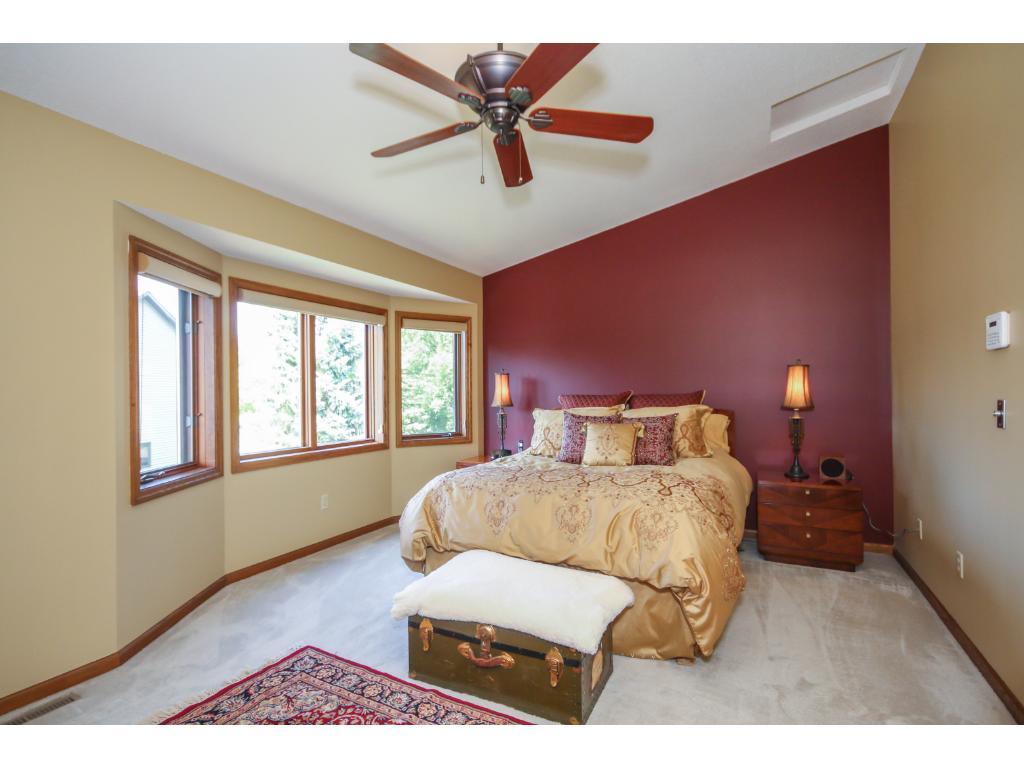The large master suite includes a bedroom with a vaulted ceiling with ceiling fan, and a large bayed window!