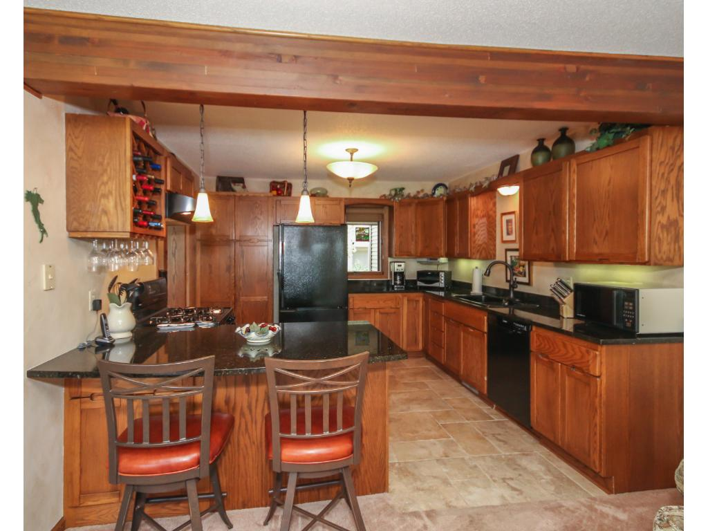 Gourmet kitchen features granite counter-tops with plenty of counter and cabinet space including the large breakfast bar!