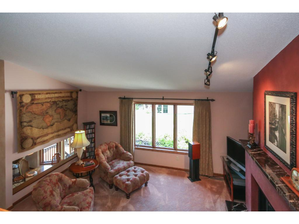 The dramatic, open, vaulted living room features a pretty fireplace and views of the backyard and pond!