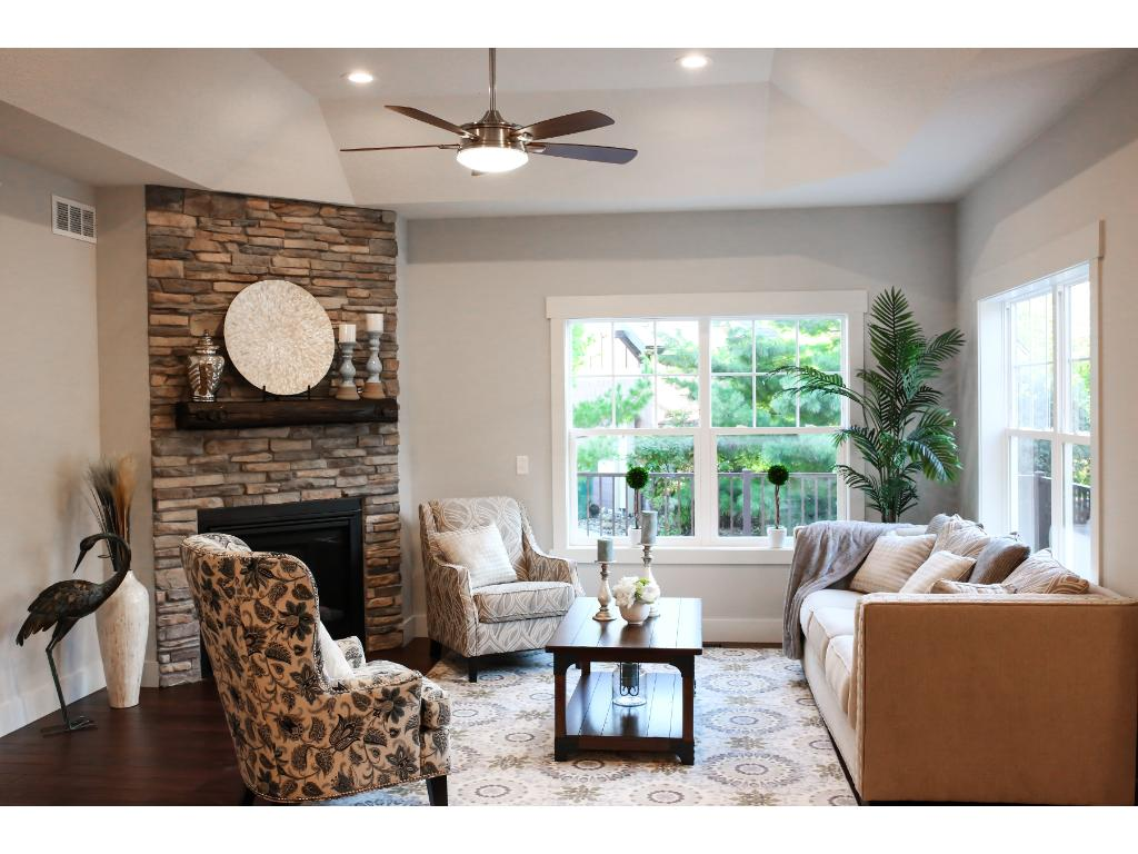 """Great room offers vaulted ceiling, stone fireplace, and 42"""" barn door."""