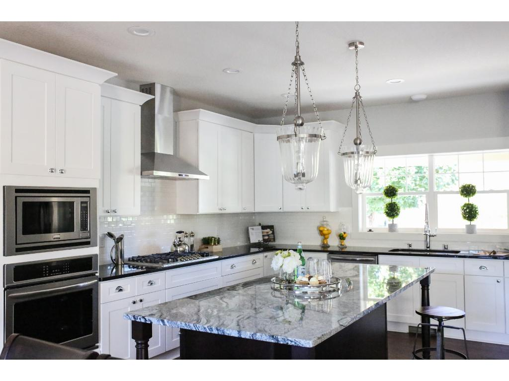 Large kitchen features white enameled cabinets, granite countertops and SS appliances.